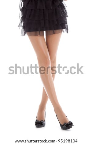Long pretty woman legs, isolated on white background, sexy female legs in shoes on a heel, in short black dress posing, series photo - stock photo