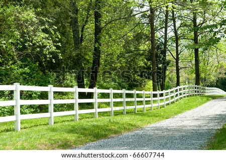 Long, private, country road along a white picket fence. - stock photo