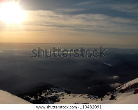 Long range vistas as viewed from the top of Mt. Hood in state of Oregon in the United States of America with snow on rocky boulders, blue skies, wispy clouds and sunshine - stock photo