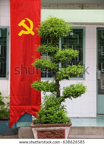 Long red banner with symbol of Vietnam hanging next to a manicured green-leafed tree in front of a government building, Vietnam