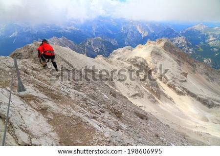 """Long ridge and climber on """"Ivano Dibona"""" via ferrata route, Dolomite Alps, Italy - stock photo"""