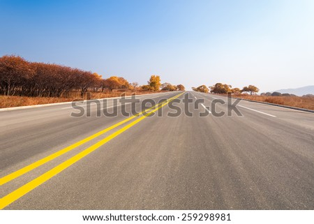 long road across the prairie in autumn - stock photo