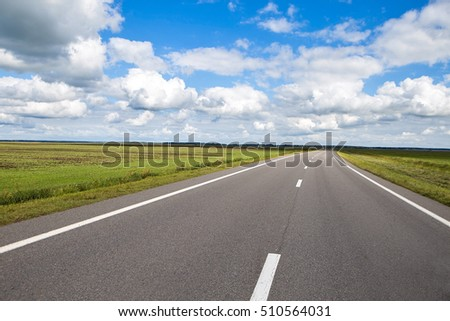 Long road. Country road landscape with sky clouds and green fields