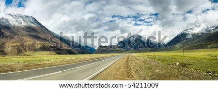 long road in mountains. Altai. panoramic image from several pictures - stock photo