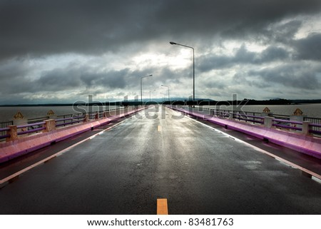 Long road through big lake - stock photo