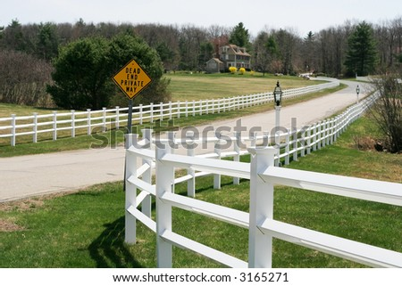 long road with fences and sign