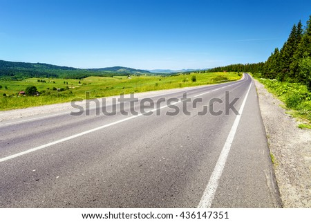 Long road with trees on roadside. Remote green hills on horizon