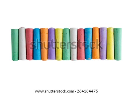 Long row of brightly colored chalk crayons in the colors of the rainbow neatly aligned centered on a white background , view from above - stock photo