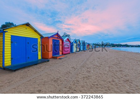 Long row of colorful bathing houses at pink sunrise in Melbourne, Australia - stock photo