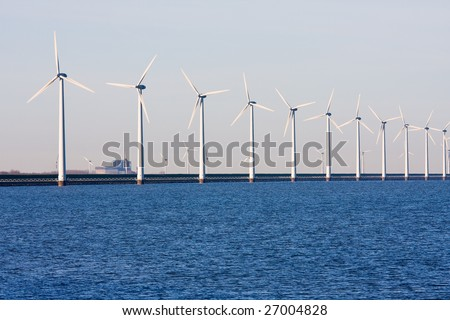 Long row of Dutch wind-turbines in the sea - stock photo