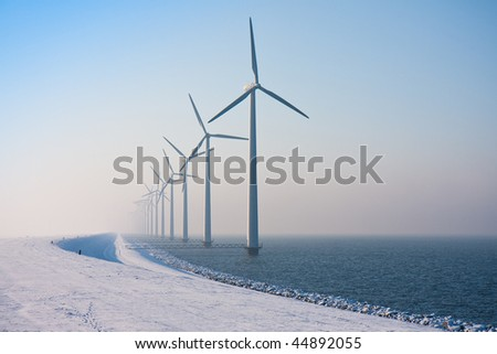 Long row of Dutch windmills disappearing in winter haze - stock photo