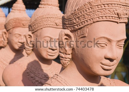 Long row of traditional statues guarding the entrance to a Buddhist temple - stock photo