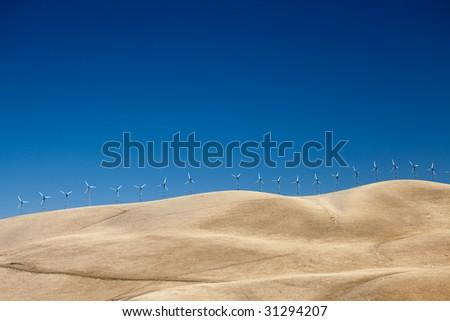 Long row of wind turbines along the ridge of a field - stock photo