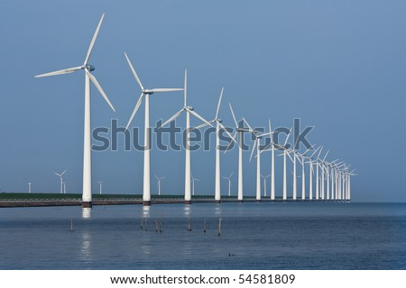 Long row of wind turbines, mirrored in the Dutch sea - stock photo