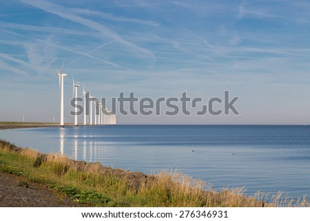 Long row off shore wind turbines along the Dutch coast - stock photo