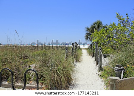 Long sand path past grasses and foliage to popular, sunny and busy Siesta Beach on Siesta Key.  - stock photo