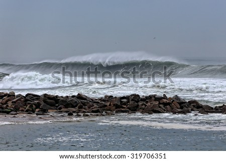 Long sea wave approaching the portuguese coast in a windy autumn afternoon - stock photo