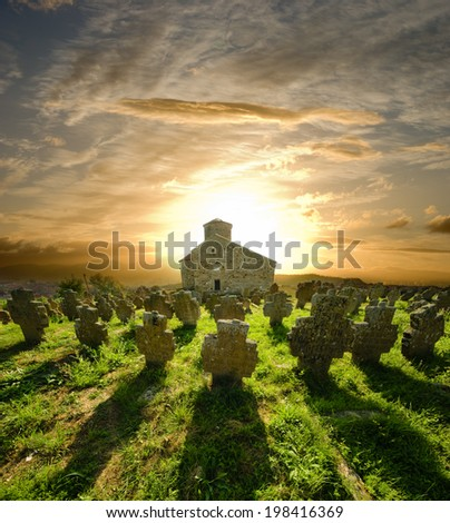 long shadow church tombstones at the sunset, Serbia - stock photo