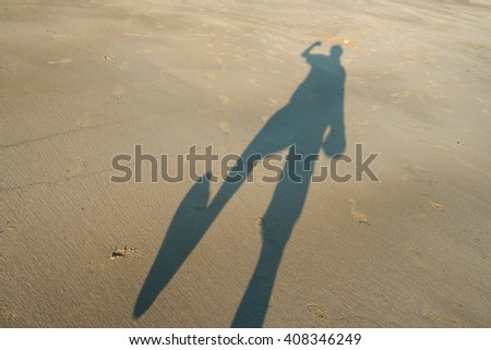 Long shadow of the man standing on the sandy beach - stock photo