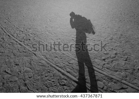 Long shadow of the man standing on the sandy beach black and white filter - stock photo