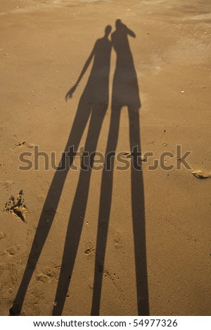 Long shadow of young couple on beach sand - stock photo