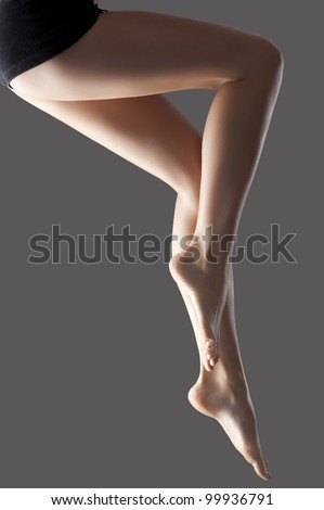 Long shaved pretty woman legs isolated with a fashion light - stock photo