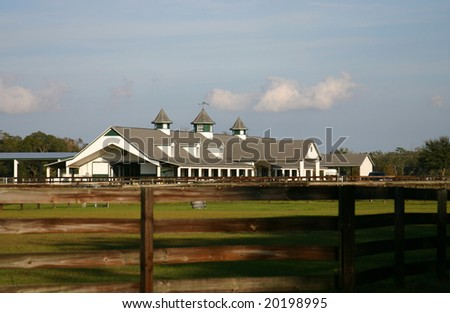 Long shot of a white multi-stall horse barn surrounded by green pastures and brown plank fences. Farm is framed against a clear blue sky.  PHOTOID: Willingham-00007 - stock photo