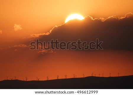 Long shot of sunset over mountains profile with modern windmills, orange sky