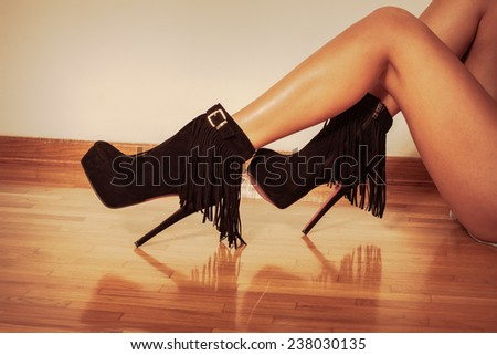 long slim woman legs in black ankle high heel fringe boot indoor shot on parquet against wall retro colors - stock photo