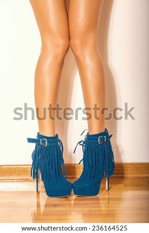long slim woman legs in blue  ankle high heel fringe boot indoor shot on parquet against wall - stock photo