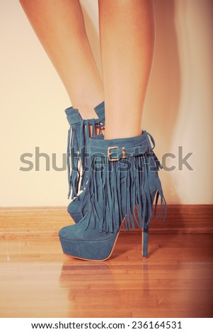 long slim woman legs in blue  ankle high heel fringe boot indoor shot on parquet against wall retro colors - stock photo