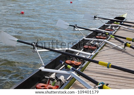 Long sport boat with oars stands at wooden pier at sunny day. - stock photo