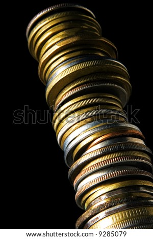 long stack of coins from below on black background - stock photo