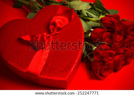 Long stem red roses and box of candy on a red background.  Valentine's day gift, symbol of love and passion - stock photo