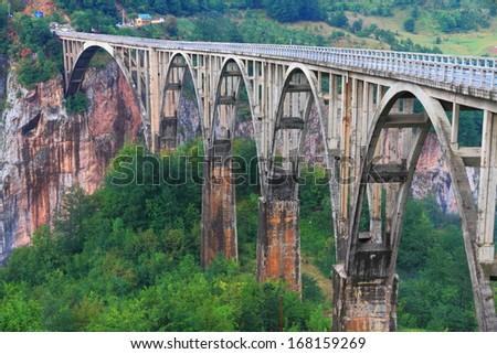 Long stone bridge across deep canyon - stock photo