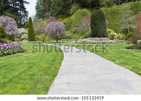 Long stone pathway into the garden of trees and flowers