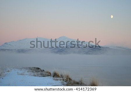 long stone pier going into dense ice fog over fjord with snowy mountain background and colorful dawn sky - stock photo