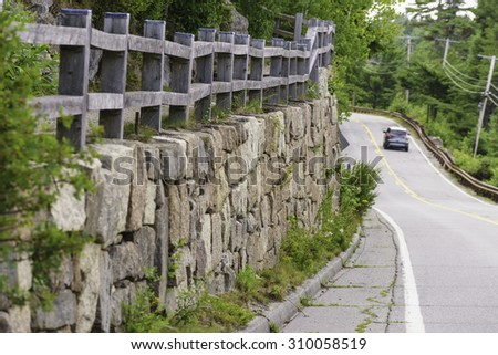 Long stone wall topped by wooden fence along a winding road on Mount Desert Island, Maine, USA, in summer - stock photo
