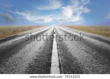 Long straight asphalt road and blue cloudy summer sky - stock photo
