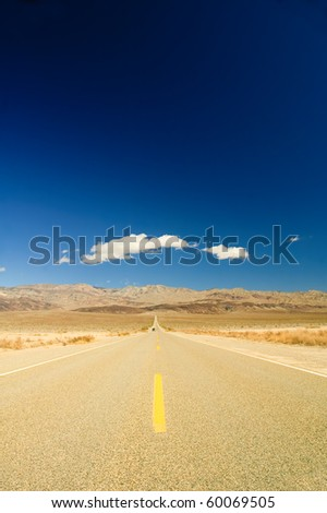 long straight road across Death Valley with a distant motor vehicle coming towards the camera, a deep blue sky late in the afternoon, and a small puffy clouds in the sky - stock photo