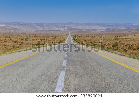 Long Straight Road Highway crossing through the desert and goes to horizon on background of blue sky