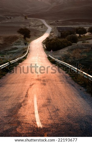 long straight road middle of rural area - stock photo