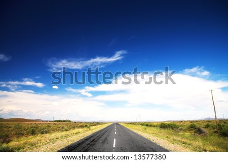 Long straight road under a dramatic dark blue saturated sky with some fine white clouds, and lined with some greenery and small shrubs - stock photo