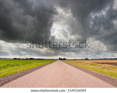 Long Straight Road with Dark Cloudy Sky as a Concept for an Uncertain Economic Future - stock photo