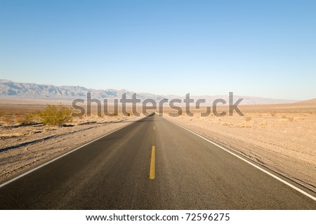 Long straight tarmac road heading into the desert of Death Valley - stock photo