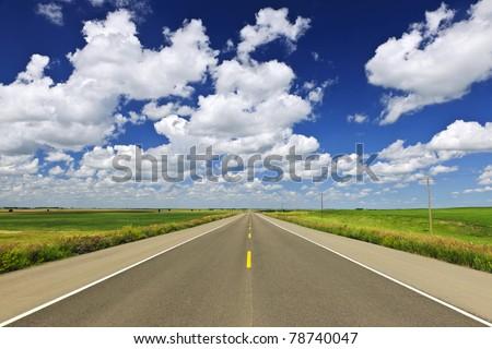 Long stretch of flat highway in Saskatchewan prairies, Canada - stock photo