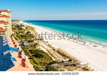 Long stretch of Miramar Beach, in Destin, Florida and the emerald green waters of the Gulf of Mexico. - stock photo