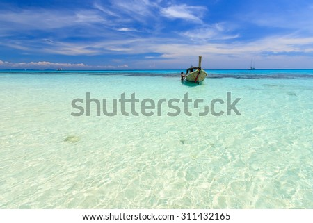 Long tail boat against blue sky and crystal clear sea . Koh Rok island, Krabi, Thailand. - stock photo