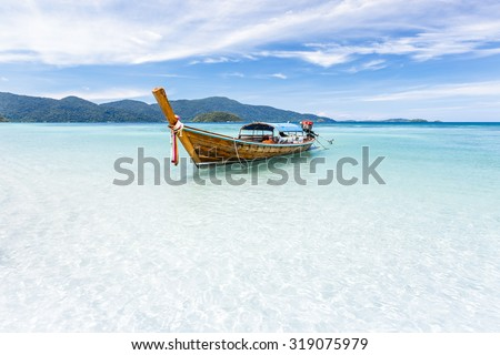 Long-tail boat floating on crystal clear sea water at tropical island, Andaman sea, Krabi, Thailand - stock photo