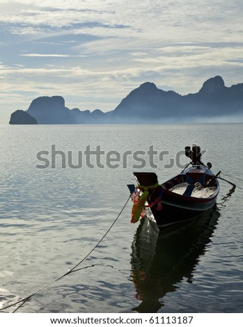 Long-tail Boat in Thailand at dawn with fog in the Background.